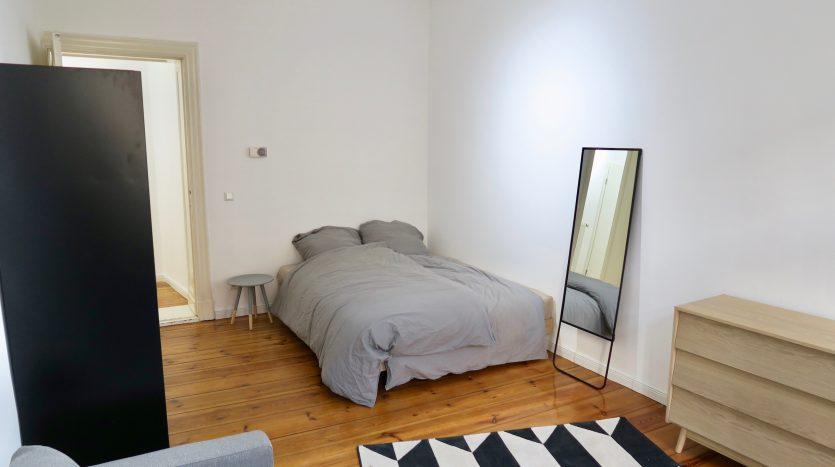 Chambre avec lit double, miroir, tapis et rangements